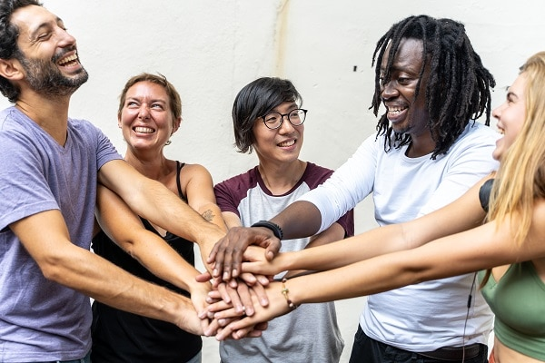 group of young people from different ethnic groups smiling and putting their hand together in a team gesture