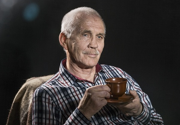 Waist up portrait of smiling pleased gaffer with kind face drinking coffee  isolated on black background with copy space.